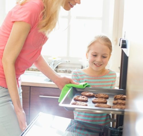 Happy mother and daughter removing cookie tray from oven at home spending quality time
