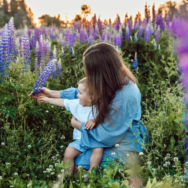 mom holding child on lap in field of purple flowers