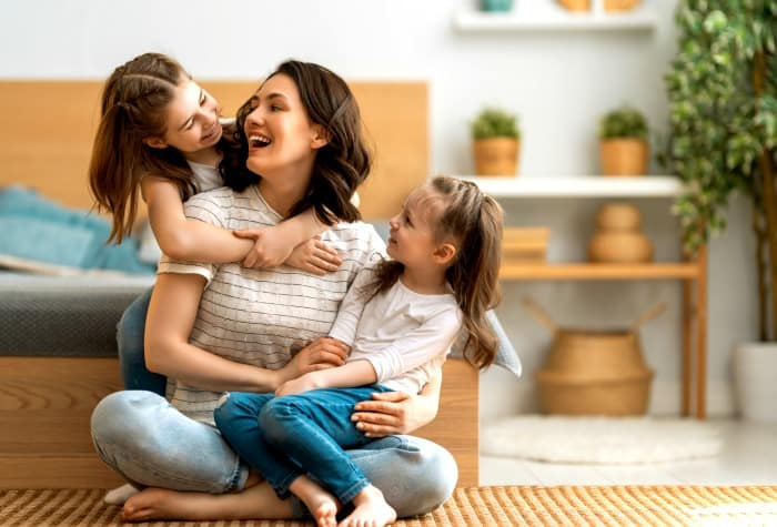 woman being a stay at home mom holding her children